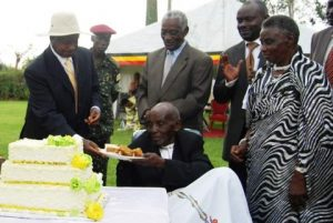 President Museveni (L) serves cake to Mzee Rubongoya in Kabarole District on Saturday. PHOTO BY Ruth Katusabe.