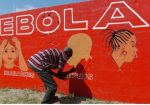 A Liberian man paints on a wall as part of a sensitisation programme about the deadly Ebola virus. Photograph: Ahmed Jallanzo/EPA