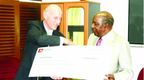 FINANCE Minister Alexander Chikwanda (right) receives a dummy cheque from Zanaco managing director Bruce Dick at the Ministry of Finance in Lusaka yesterday. Picture by CLEVER ZULU