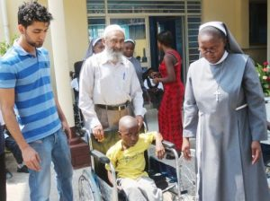 Italian Hospital Acting Administrator Sr. Ireen Kunda  and Donations Coordinator Haroon Ghumra placing   Sylvester Chali,6 years old and Livingstone resident,  in his newly donate wheel chair while looking on is Cardinal Distributors MD Safwaan Patel.