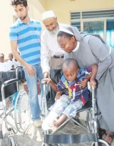 Italian Hospital Acting Administrator Sr. Ireen Kunda  placing   Philip Kusa, 4 years old and Chipata resident,  in his newly donate wheel chair while looking on are Cardinal Distributors MD Safwaan Patel and Donations Coordinator Haroon Ghumra.