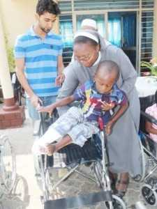 Italian Hospital Acting Administrator Sr. Ireen Kunda  placing   Philip Kusa, 4 years old and Chipata resident,  in his newly donate wheel chair while looking on is Cardinal Distributors MD Safwaan Patel..