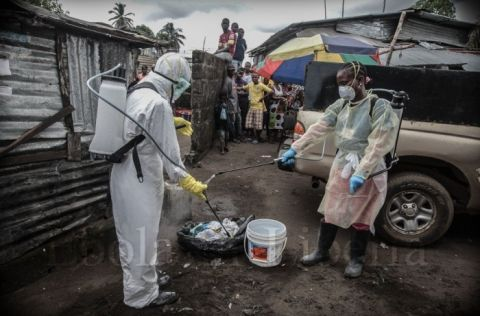 Members of the Liberian Red Cross burial team disinfect each other - Ebola crisis in Liberia