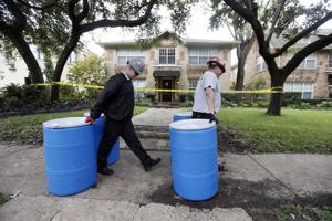 Protect Environmental workers move disposal barrels to a staging area outside the apartment of a hea…