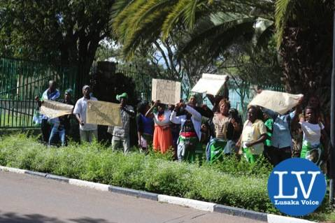 Score of PF cadres at the the gate of National Assembly of Zambia chatting slogans and showing off placards against Chongwe MP Hon Sylvia Masebo on Tuesday afternoon.