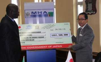 Japanese Ambassador to Zambia, Koishi Koinuma, presenting a US$1.5 million cheque to Home Affairs Minister, Davis Mwila in Lusaka, Zambia on Tuesday 24 March 2015. The funds will go towards the refugee and local integration programme in Zambia. Picture courtesy of UNHCR